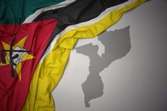 Κυματίζοντας ζωηρόχρωμοι εθνική σημαία και χάρτης της Μοζαμβίκης απεικόνιση αποθεμάτων
