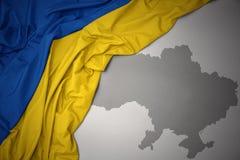 Κυματίζοντας ζωηρόχρωμοι εθνική σημαία και χάρτης της Ουκρανίας Στοκ Εικόνα