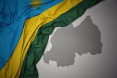 Κυματίζοντας ζωηρόχρωμοι εθνική σημαία και χάρτης της Ρουάντα απεικόνιση αποθεμάτων