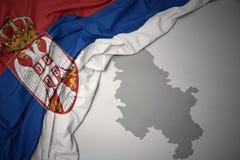 Κυματίζοντας ζωηρόχρωμοι εθνική σημαία και χάρτης της Σερβίας Στοκ φωτογραφίες με δικαίωμα ελεύθερης χρήσης