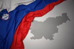 Κυματίζοντας ζωηρόχρωμοι εθνική σημαία και χάρτης της Σλοβενίας Στοκ Φωτογραφία