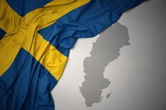 Κυματίζοντας ζωηρόχρωμοι εθνική σημαία και χάρτης της Σουηδίας Στοκ φωτογραφία με δικαίωμα ελεύθερης χρήσης