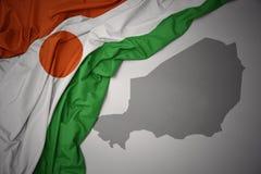 Κυματίζοντας ζωηρόχρωμοι εθνική σημαία και χάρτης του Νίγηρα ελεύθερη απεικόνιση δικαιώματος