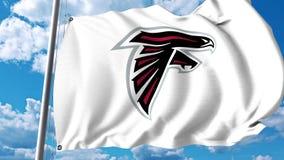 Κυματίζοντας σημαία με το επαγγελματικό λογότυπο ομάδων των Atlanta Falcons Εκδοτική τρισδιάστατη απόδοση Στοκ Φωτογραφίες