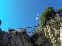 Κυματίζοντας σημαία της Ελλάδας στην κορυφή ενός απότομου βράχου φιλμ μικρού μήκους