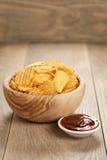 Κυματισμένα τσιπ πατατών με την πάπρικα και bbq τη σάλτσα στο ξύλινο κύπελλο Στοκ φωτογραφίες με δικαίωμα ελεύθερης χρήσης