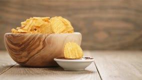 Κυματισμένα τσιπ πατατών με την πάπρικα και bbq τη σάλτσα στο ξύλινο κύπελλο Στοκ Εικόνα