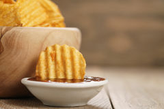 Κυματισμένα τσιπ πατατών με την πάπρικα και bbq τη σάλτσα στο ξύλινο κύπελλο Στοκ εικόνα με δικαίωμα ελεύθερης χρήσης