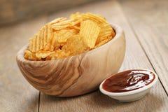 Κυματισμένα τσιπ πατατών με την πάπρικα και bbq τη σάλτσα στο ξύλινο κύπελλο Στοκ Εικόνες