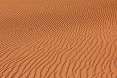 Κυματισμένη κόκκινη καφετιά σύσταση άμμου ερήμων ή παραλιών ανασκόπηση κυματιστή Στοκ Εικόνα