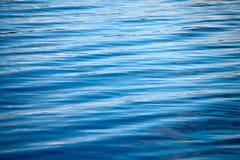 Κυματισμοί σε ένα μπλε υπόβαθρο νερού Στοκ Εικόνες