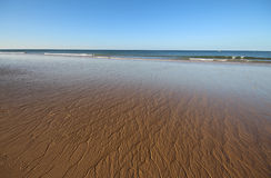 Κυματιστή άμμος στην ανοικτή παραλία Στοκ Φωτογραφία