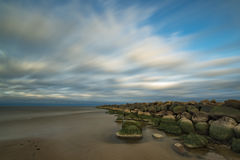 Κυματοθραύστης και χρωματισμένα ανατολή σύννεφα Στοκ Εικόνες