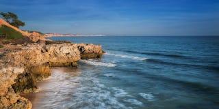 Κυματωγή θάλασσας στην παραλία Albufeira και βουνό στην Πορτογαλία Στοκ Εικόνα