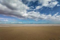Κυματωγή σε μια ήπια κεκλιμένη παραλία με το νεφελώδη ουρανό στοκ φωτογραφίες με δικαίωμα ελεύθερης χρήσης