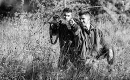 Κυνήγι με τον ελεύθερο χρόνο χόμπι φίλων Χόμπι για την πραγματική έννοια ατόμων Κυνηγοί με τα τουφέκια στο περιβάλλον φύσης Φίλος στοκ εικόνες
