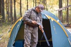 Κυνηγετικό όπλο φόρτωσης κυνηγών στο στρατόπεδο κυνηγιού Στοκ εικόνες με δικαίωμα ελεύθερης χρήσης