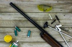 Κυνηγετικό όπλο με τον καθαρισμό των προμηθειών στο αγροτικό ξύλινο υπόβαθρο Στοκ Φωτογραφίες