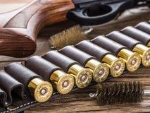 Κυνηγετικό όπλο δράσης αντλιών, κασέτα 12 μετρητών και έμβολο στον ξύλινο Στοκ Εικόνες