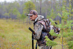 Κυνηγός που κρατά ένα πυροβόλο όπλο και που περιμένει το θήραμα Στοκ Εικόνα