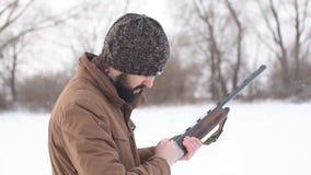 Κυνηγός που οπλίζει το πυροβόλο όπλο πριν από το κυνήγι υπαίθρια κίνηση αργή απόθεμα βίντεο