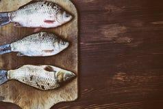 Κυπρίνος ψαριών στις κλίμακες στον τέμνοντα πίνακα κουζινών Στοκ Φωτογραφία