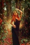 Κυρία γοητείας redhair με το στεφάνι του λυκίσκου στο μαγικό δάσος Στοκ εικόνα με δικαίωμα ελεύθερης χρήσης