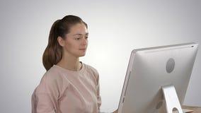 Κυρία γραφείων στο ρόδινο πουλόβερ με μια τρίχα ουρών πόνι που λειτουργεί στον υπολογιστή στο υπόβαθρο κλίσης απόθεμα βίντεο