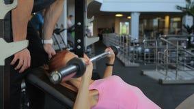 Κυρία ικανότητας που κάνει barbell τον Τύπο πάγκων κάτω από τη επίβλεψη εκπαιδευτών στη γυμναστική φιλμ μικρού μήκους