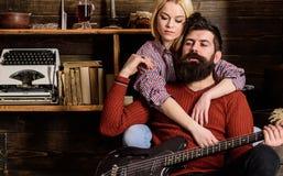 Κυρία και άτομο με τη γενειάδα στην ονειροπόλο κιθάρα αγκαλιασμάτων και παιχνιδιών προσώπων Το ζεύγος στο ξύλινο εκλεκτής ποιότητ Στοκ φωτογραφία με δικαίωμα ελεύθερης χρήσης