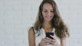 Κυρία με την κυματιστή τρίχα που χρησιμοποιεί το smartphone απόθεμα βίντεο