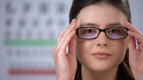 Κυρία με τη θολωμένη όραση που βάζει στα γυαλιά και που χαμογελά, βελτίωση οράματος απόθεμα βίντεο