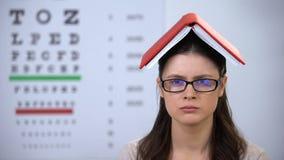 Κυρία με το βιβλίο στο κεφάλι που κοιτάζει στη κάμερα, καταπονημένος σπουδαστής που προετοιμάζεται για τη δοκιμή φιλμ μικρού μήκους