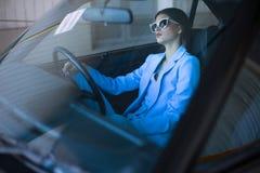 Κυρία μόδας που οδηγεί ένα αυτοκίνητο σε ένα μπλε κοστούμι Μοντέρνη συνεδρίαση κοριτσιών στο τιμόνι αυτοκινήτων και εκμετάλλευσης Στοκ εικόνα με δικαίωμα ελεύθερης χρήσης