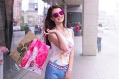 Κυρία μόδας στα γυαλιά που κρατά τις συσκευασίες των καταστημάτων και των χαμόγελων Στοκ εικόνες με δικαίωμα ελεύθερης χρήσης