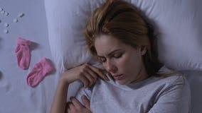 Κυρία που βρίσκεται στο κρεβάτι κοντά στις ρόδινες κάλτσες μωρών και που ανατρέπει την αυτοκτονία χαπιών μετά από το misbirth φιλμ μικρού μήκους