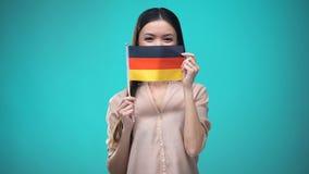 Κυρία που καλύπτει το πρόσωπο με τη γερμανική σημαία, μαθαίνοντας τη γλώσσα, την εκπαίδευση και το ταξίδι απόθεμα βίντεο