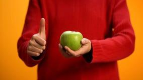Κυρία που κρατά το πράσινο χέρι μήλων που παρουσιάζει αντίχειρες, πρόχειρο φαγητό φρούτων, υγιής διατροφή στοκ φωτογραφία με δικαίωμα ελεύθερης χρήσης