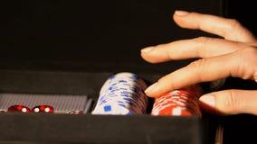 Κυρία που παίρνει το τσιπ πόκερ από την περίπτωση, που παρουσιάζει στη κάμερα, που προετοιμάζεται για το παιχνίδι χαρτοπαικτικών  φιλμ μικρού μήκους