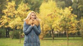 Κυρία που φορά το μοντέρνο παλτό που παγώνει περιμένοντας το φίλο, σκηνή φθινοπώρου φιλμ μικρού μήκους