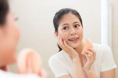 Κυρία που χρησιμοποιεί το καλλυντικό πρόσωπο λήξης σφουγγαριών makeup Στοκ Φωτογραφία