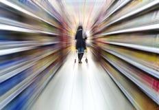 Κυρία που ωθεί ένα κάρρο αγορών Στοκ Φωτογραφίες