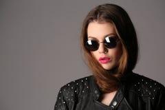 Κυρία στα γυαλιά ηλίου στερεωμένων δέρματος σακακιών και κύκλων κλείστε επάνω Άσπρη ανασκόπηση Στοκ Εικόνες