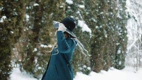 Κυρία στις πράσινες περιστροφές καπέλων και παλτών κάτω από το μειωμένο χιόνι στο δάσος φιλμ μικρού μήκους