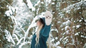 Κυρία στις πράσινες περιστροφές παλτών και καπέλων γύρω στο χειμερινό δάσος απόθεμα βίντεο