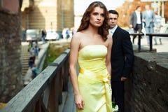 Κυρία στους κίτρινους περιπάτους φορεμάτων μακριά στην ξύλινη γέφυρα Στοκ Εικόνες