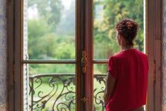 Κυρία στο κόκκινο που φαίνεται έξω παράθυρα σε έναν πολύβλαστο κήπο χωρών έξω Στοκ Φωτογραφίες