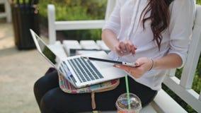 Κυρία στο πάρκο που χρησιμοποιεί το lap-top και μια ταμπλέτα Στοκ φωτογραφία με δικαίωμα ελεύθερης χρήσης