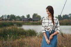 κυρία χωρών που στέκεται ενάντια στη λίμνη στο αγρόκτημα με την ψάρι-ράβδο Στοκ Φωτογραφίες