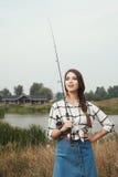 κυρία χωρών που στέκεται ενάντια στη λίμνη στο αγρόκτημα με την ψάρι-ράβδο Στοκ φωτογραφία με δικαίωμα ελεύθερης χρήσης